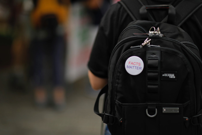 backpack with a facts matter badge on it
