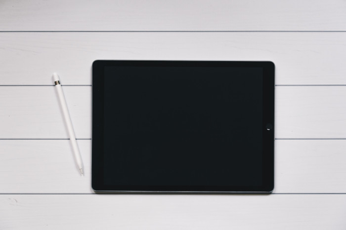 Black ipad with apple pen on a white wood surface