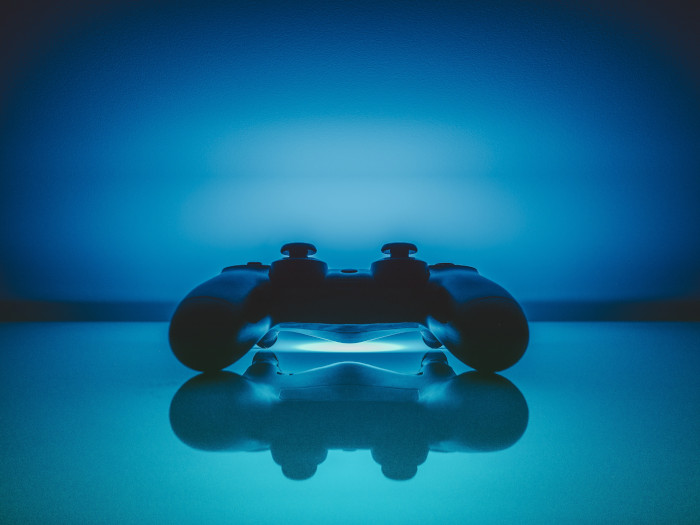 blue controller over a neon blue background