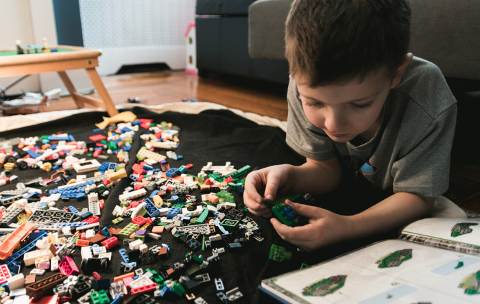 boy playing with legos and looking at instructions