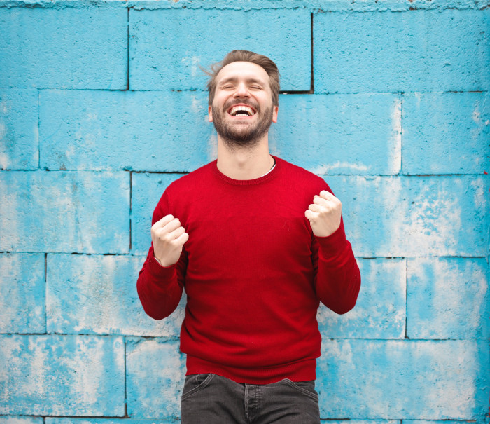 happy guy in a red shirt in front of a blue wall