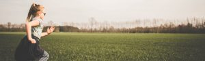 little girl running in a field