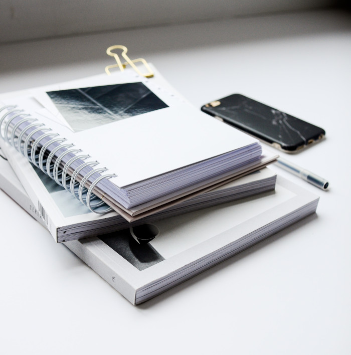 pile of books and binders on a white table
