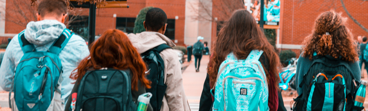 students walking with backpacks towards a school