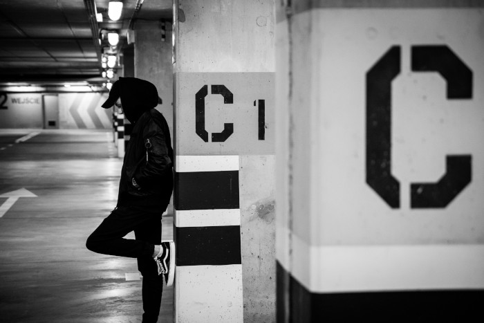 guy leaning against a column with the letter c on it