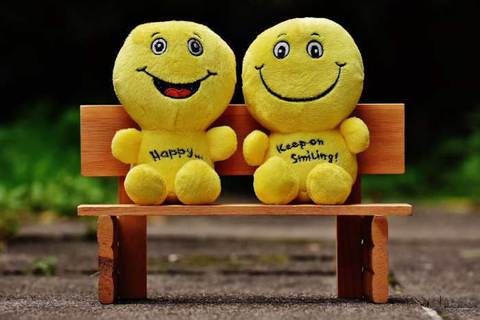 two smiling plushies sitting on a bench