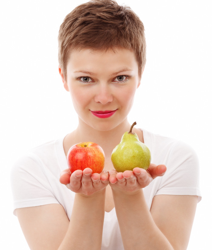 woman giving a choice between an apple and a pear