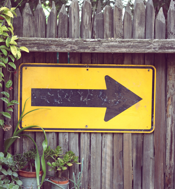 black arrow on yellow board