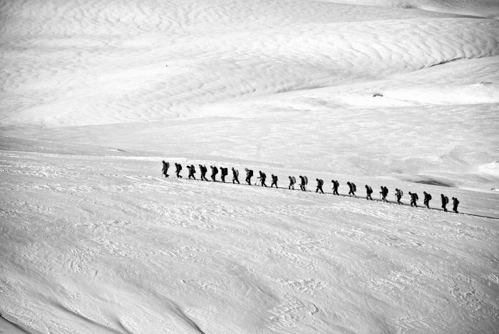 People walking in the snow in a line formation