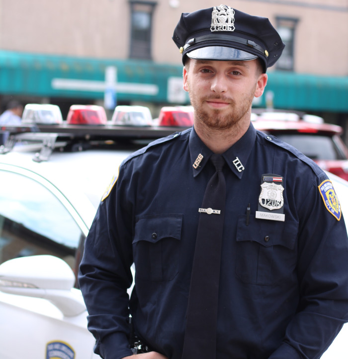 police officer in front of a cop car
