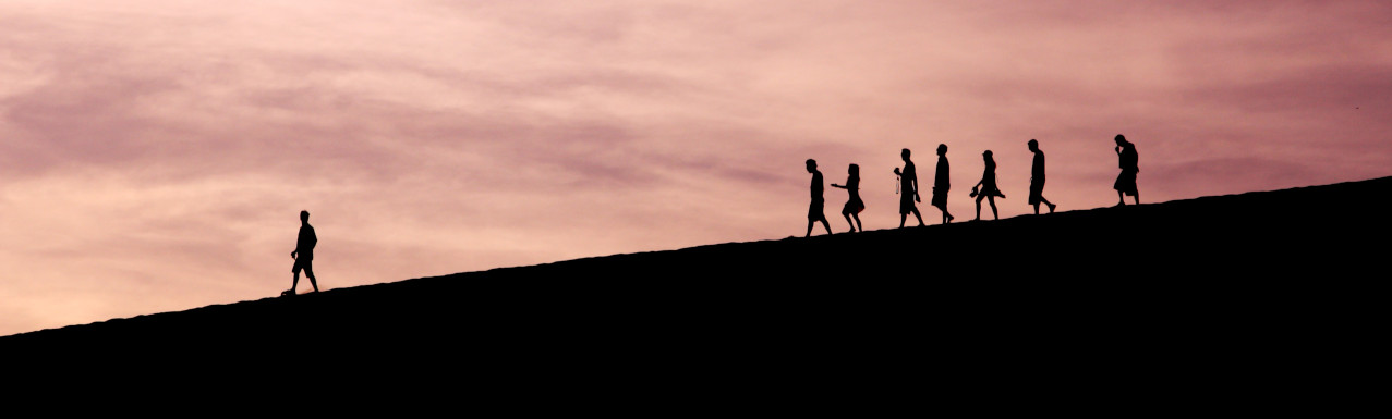 silhouette of someone being followed by a group