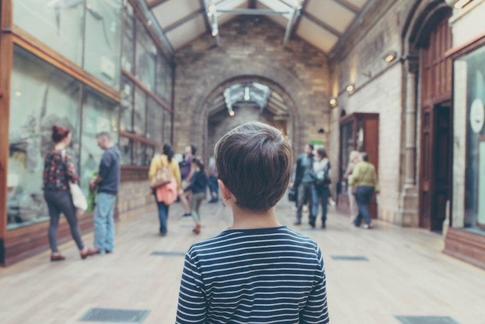 boy standing inside museum
