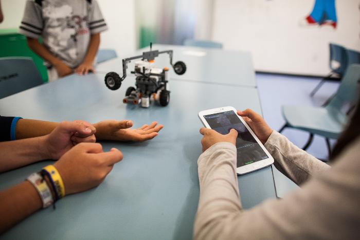 Students programming robot with tablet