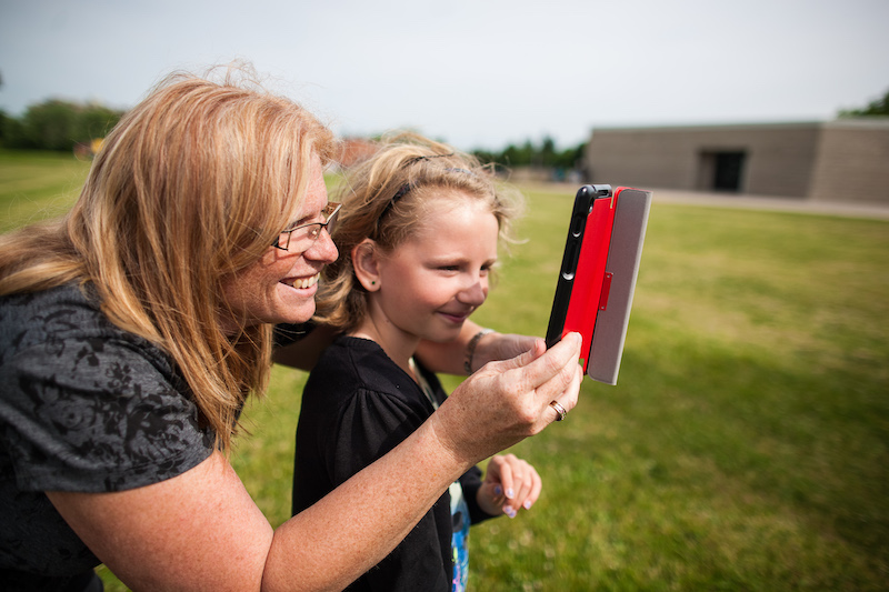 Teacher and student outside with tablet