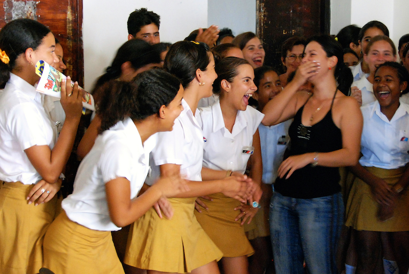 School girls laugh with their teacher
