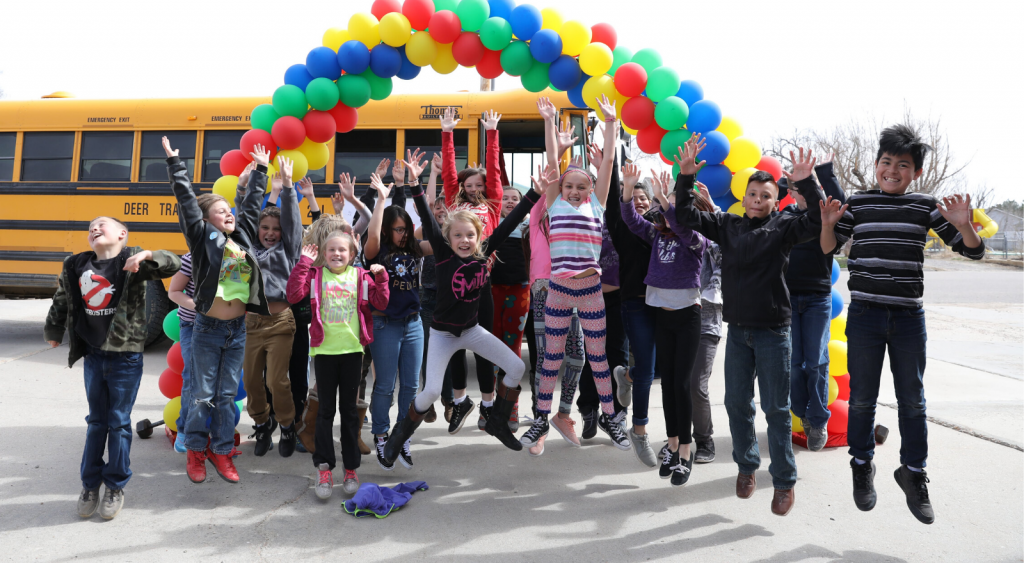Students jumping in the air outside, beside a bus with balloons