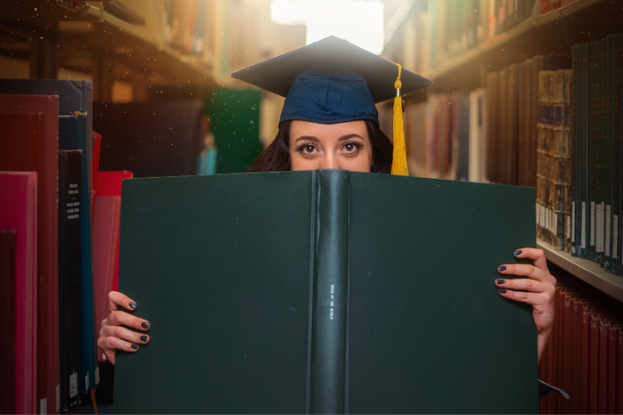 Student in grad cap holding book