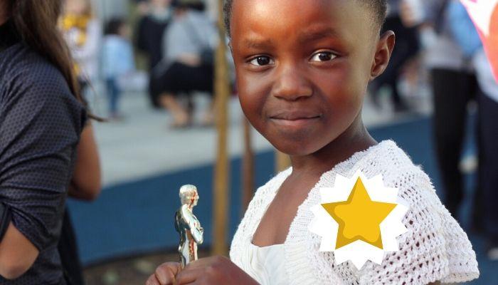 Little girl holding award