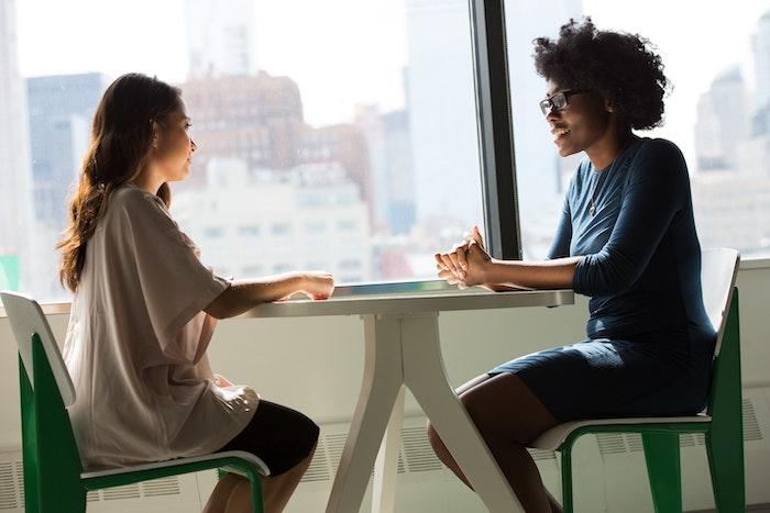 two-women-sitting-on-chairs-beside-window-Photo Pexels web
