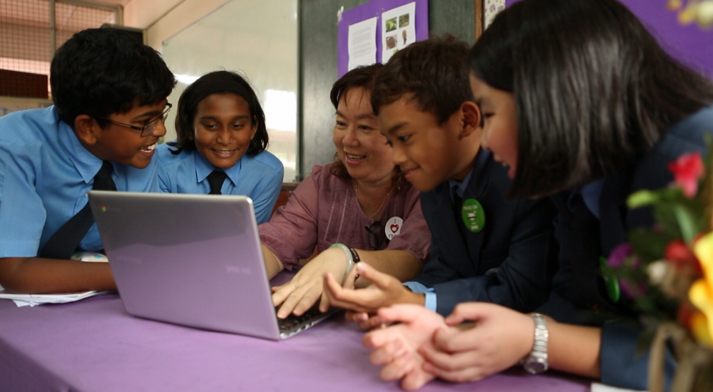 Several students with teacher looking at laptop