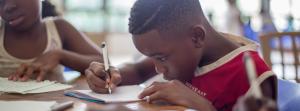 boy writing on paper near girl in classroom