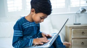 Boy using laptop while relaxing on bed in the bedrooms