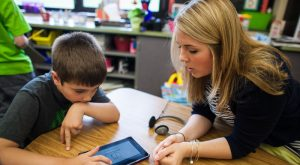 Educator working with a student on a tablet around a table