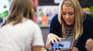 Teacher showing something to one of her students on a tablet