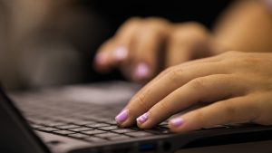Student's hands typing on a laptop