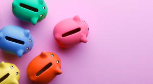 Multi colored piggy banks on a pink background
