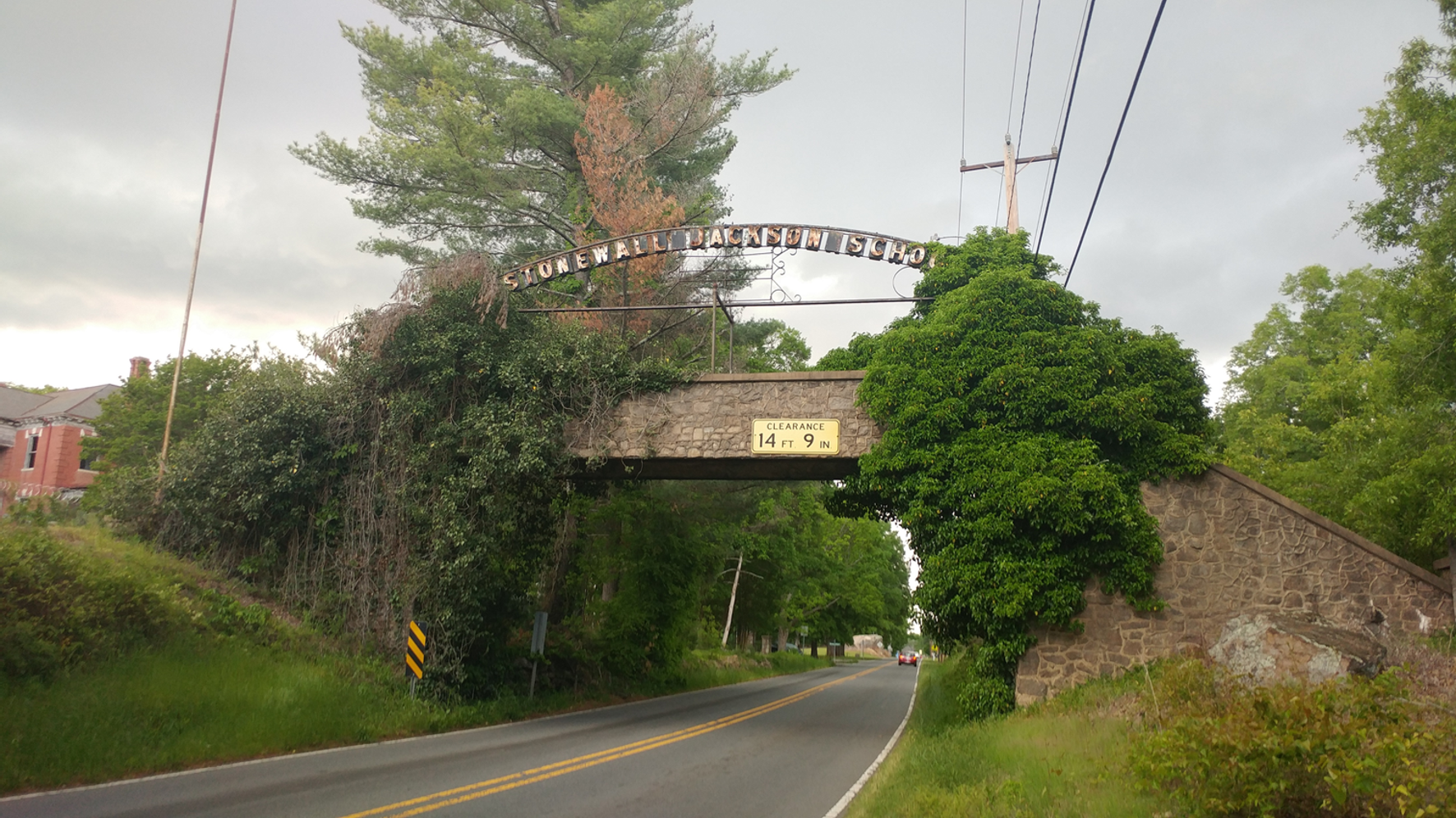 The sign for Old Stonewall above an ivy covered bridge built in 1940