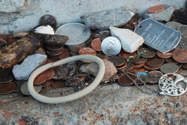 An example of some of the trinkets that are often left at the grave site. This includes jewelry, coins, cigars, dog tags, and more.