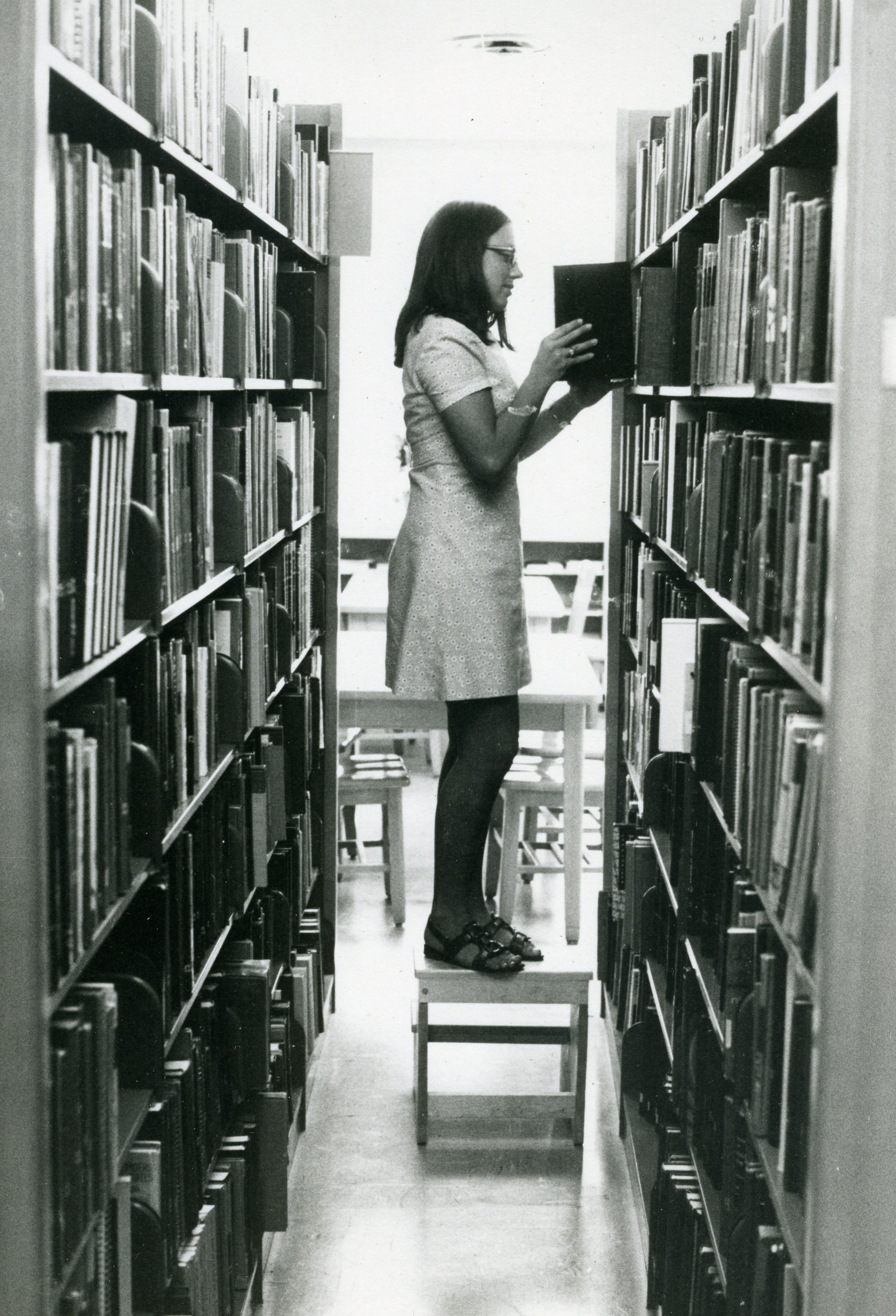 Student re-shelving books, undated