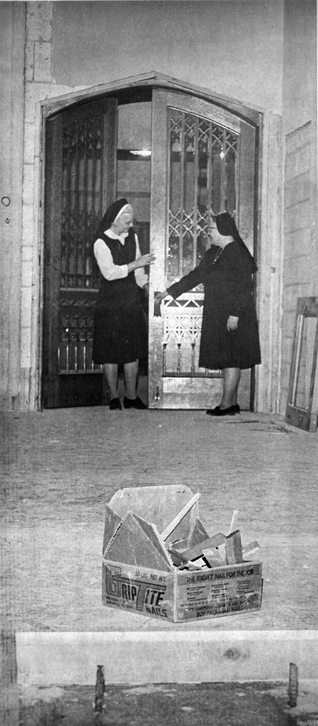 During construction of the new motherhouse at 475 Gillett St., Sisters Imogene Palen and John Baptist Shaja examine the chapel doors which came from the convent at 390 E. Division St., February 1975.