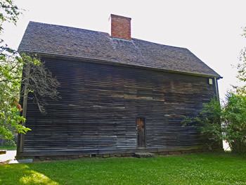 A shot of the Buttolph-Williams House. This wooden house is windowless and features a sloped roof, topped with a brick chimney.