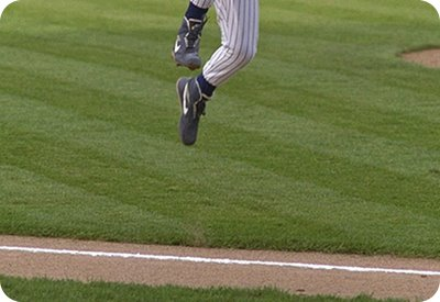 New York Yankee player jumping over the foul line after the completion of an inning.