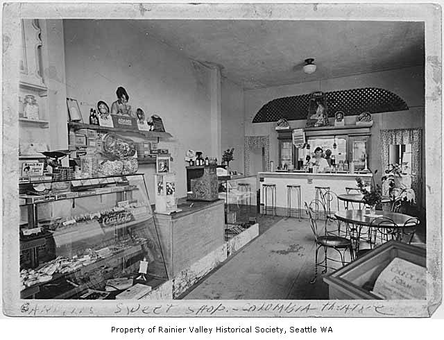 Carroll Eaton behind the counter of Carroll's Sweet Shop (in the lobby of Columbia City Theater), circa 1935