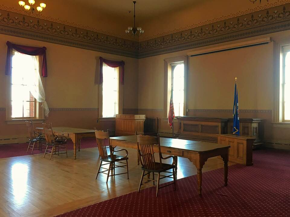 The historic courtroom features the original judge's bench, attorney's tables, witness stand, recorder's desk, and several audience chairs.