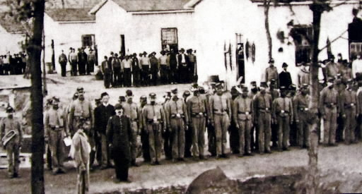 Confederate Prisoners lined up outside of prison barracks