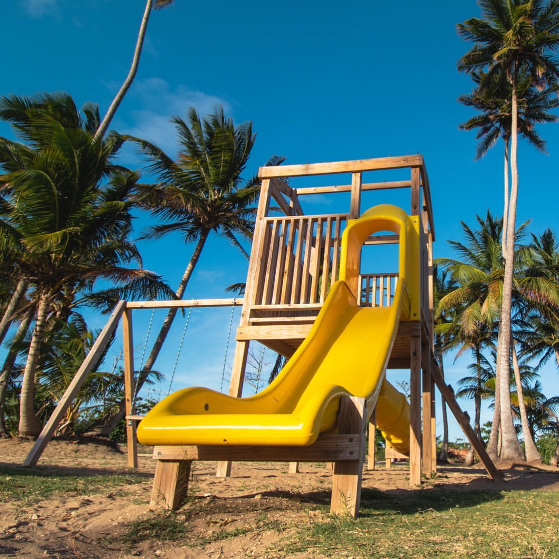 The playground area has modern equipment and a sand floor for the children's safety.