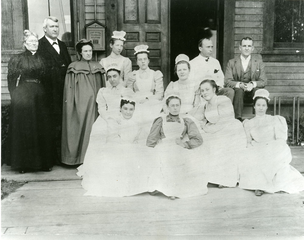 Fannie C. Paddock Memorial Hospital's first graduating class of nurses and other nursing students and staff in front of the hospital, 1897.