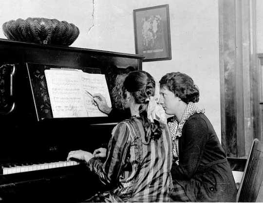 A woman giving a piano lesson to a young student in the 1920s