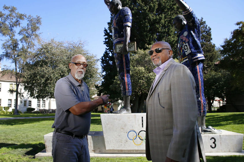 Tommie Smith & John Carlos standing in front of their statue at SJSU.