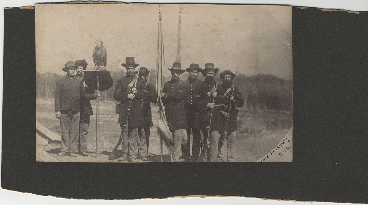 Photograph of the 8th Wisconsin Infantry Regiment Color Guard, taken after the Siege of Vicksburg. Left from right are Homiston, unidentified, Armitage, Dickersheid, McLain, Reily, Pitwch, and unidentified