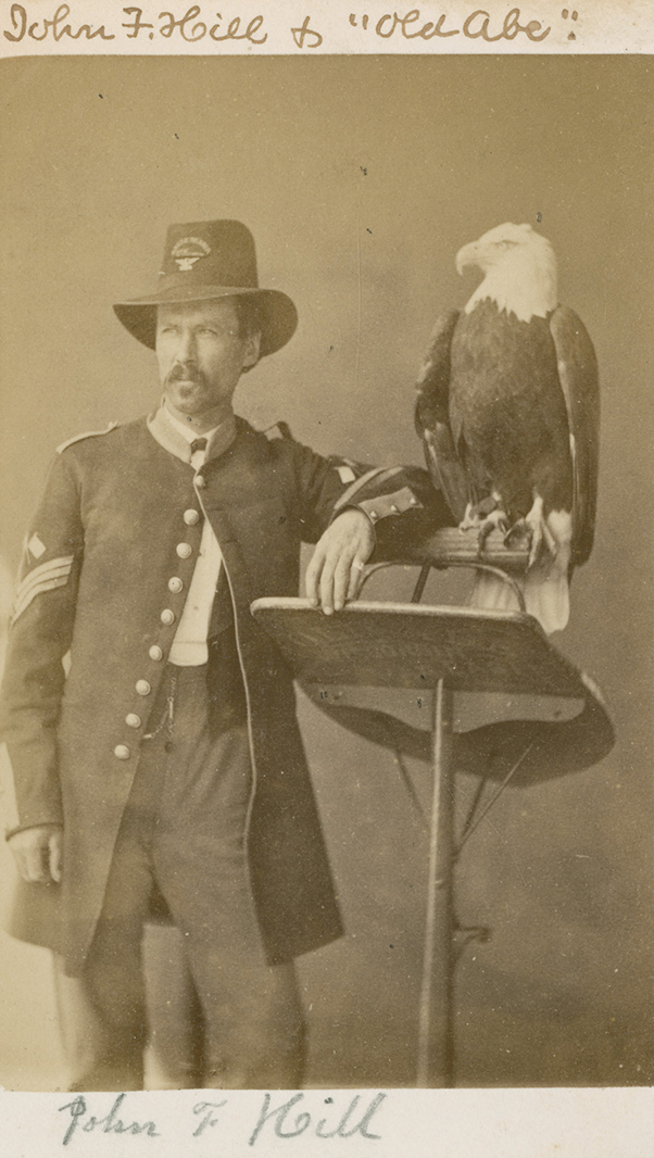 Carte-de-visite full-length portrait photograph of Old Abe the War Eagle, and handler, John F. Hill, made for the centennial in 1876. Old Abe served as the mascot for the 8th Wisconsin Infantry Regiment during the Civil War.
