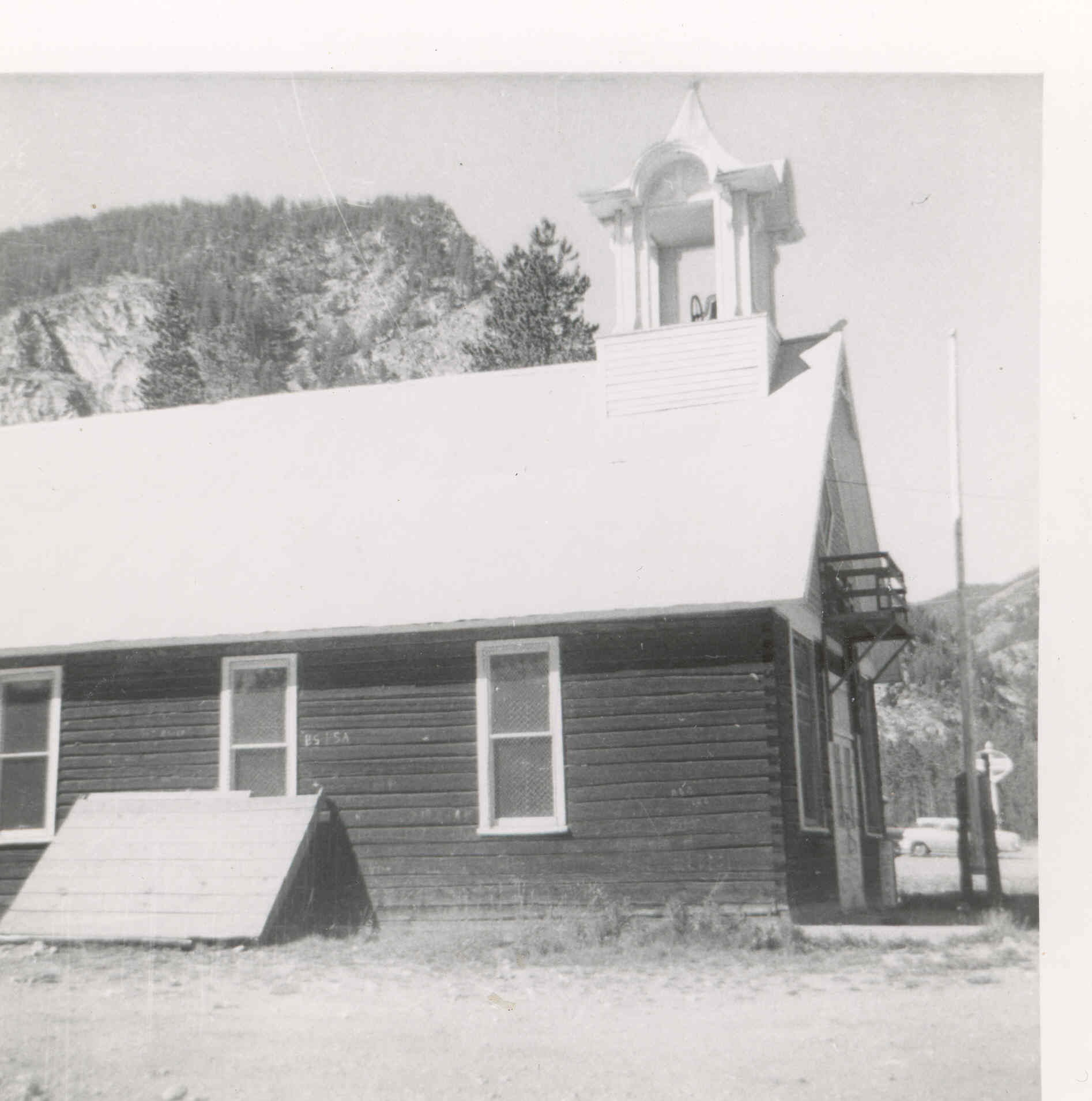 The Frisco Schoolhouse, circa 1956. Note the flag pole and the balcony above the front doors.