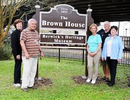 The founders of the Heritage Museum pose in front of the official museum sign.