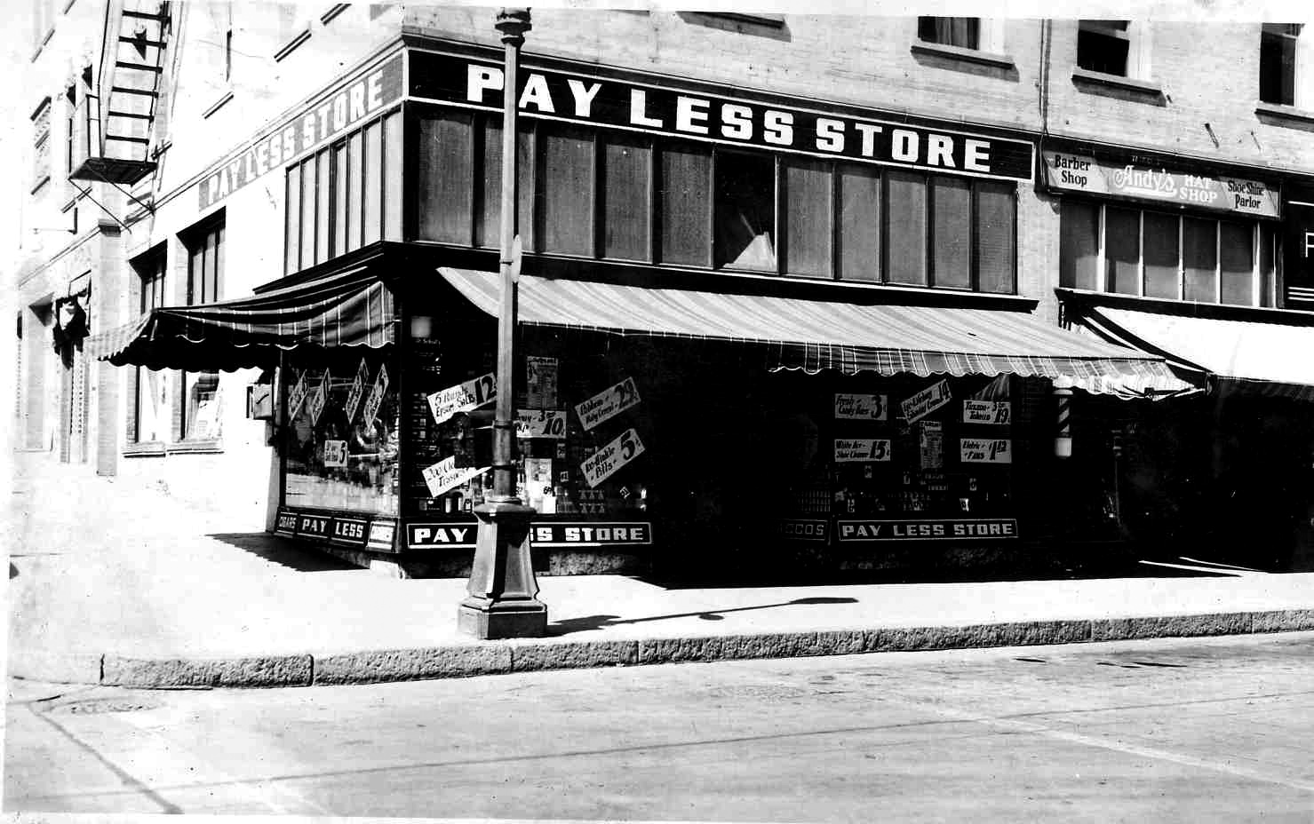 The Olympia Hotel building at the northwest corner of Palouse Street and North Wenatchee Avenue cira 1935.  Facing Wenatchee Avenue are the following business: Pay Less Store, Andy's Hat Shop, Mirror Barber Shop & Beauty Parlor and a part of Pangborn's Jewelers.