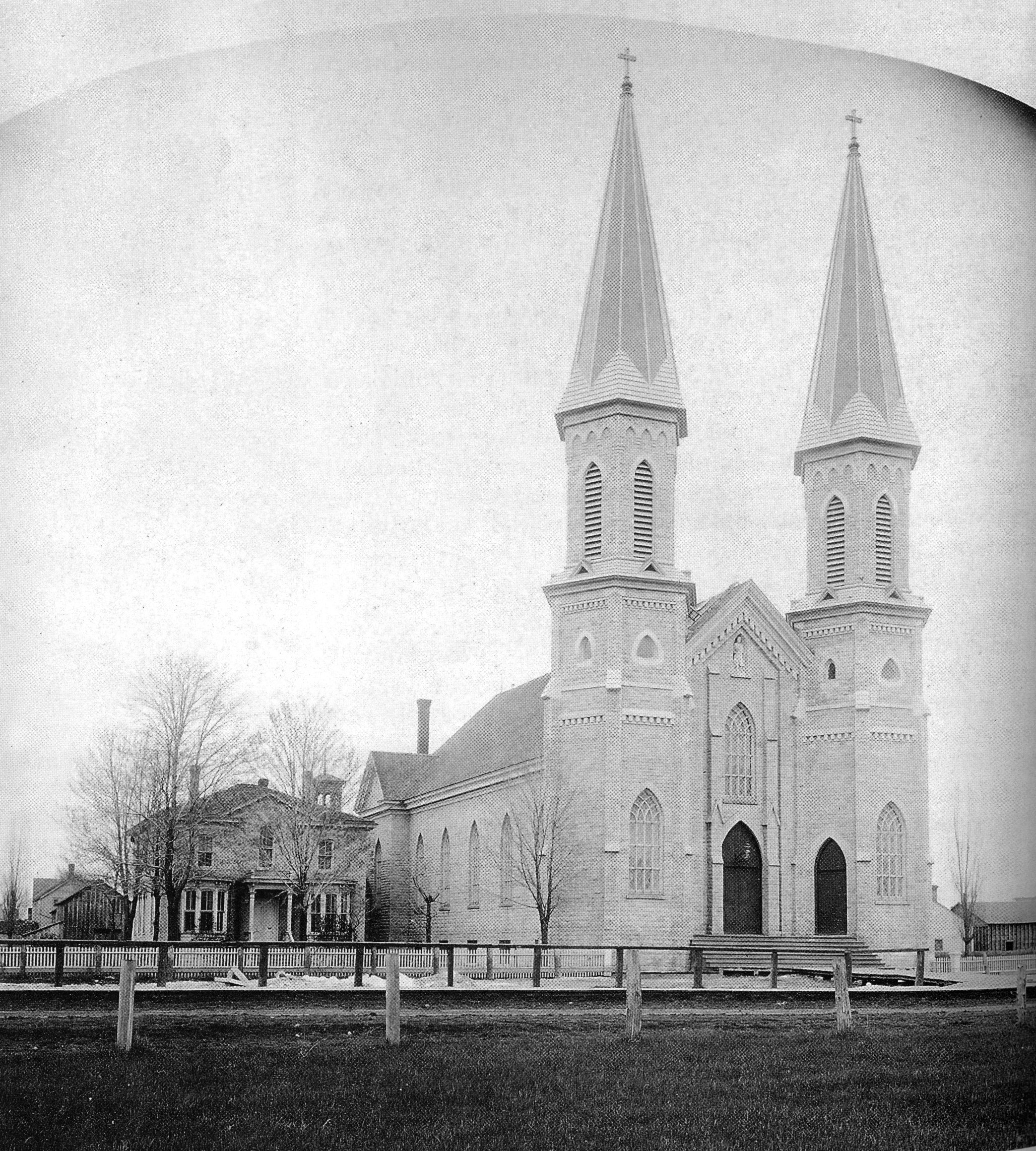 Twin steeples of St. Louis Church were finally completed in 1891.  The rectory on the left burned down in 1938.