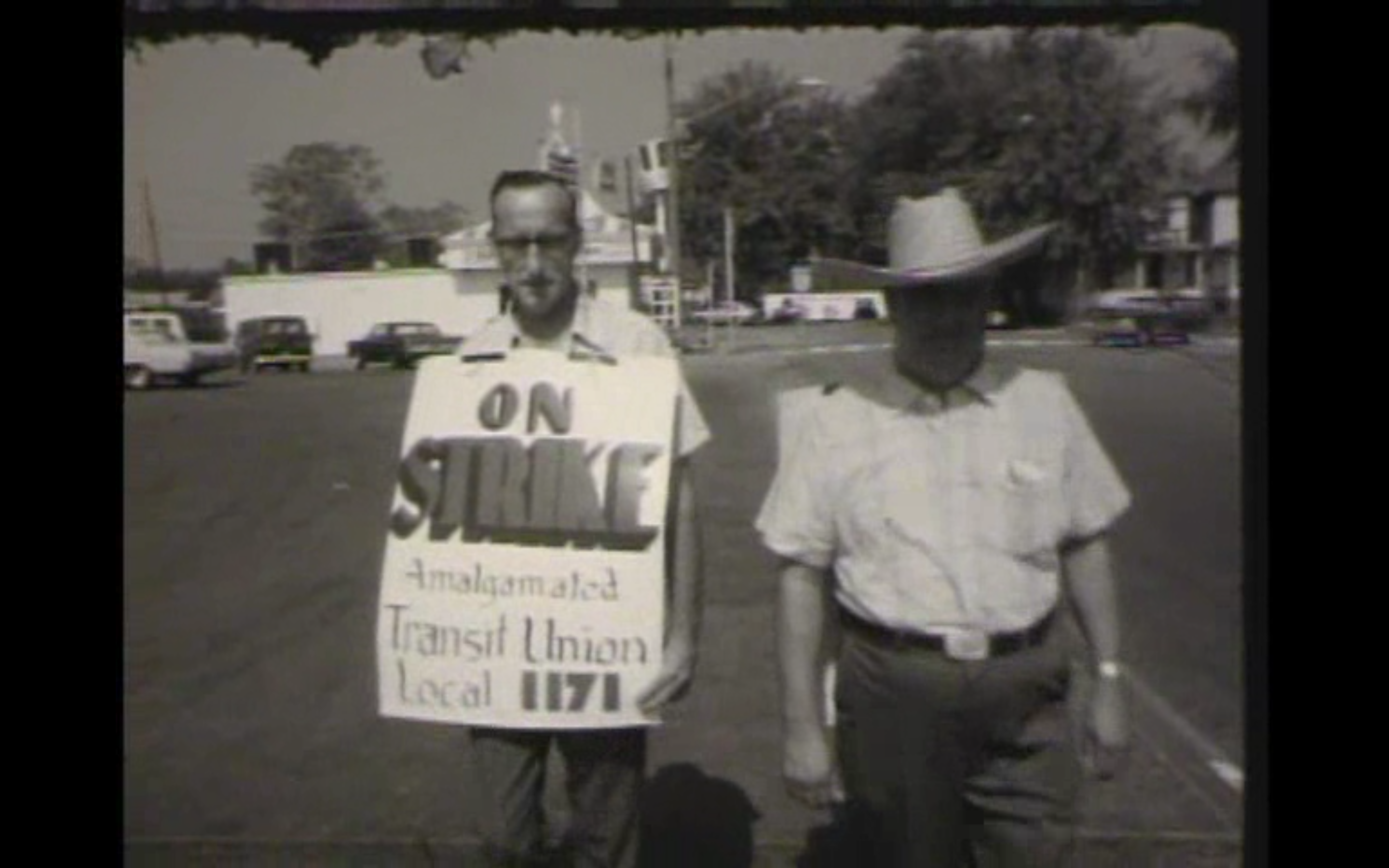 "Two employees walking outside of the Ohio Valley Bus Company's bus barn, during the 1971 strike. Employee on left is wearing a sign that reads, ""ON STRIKE Amalgamated Transit Union Local 1171"""